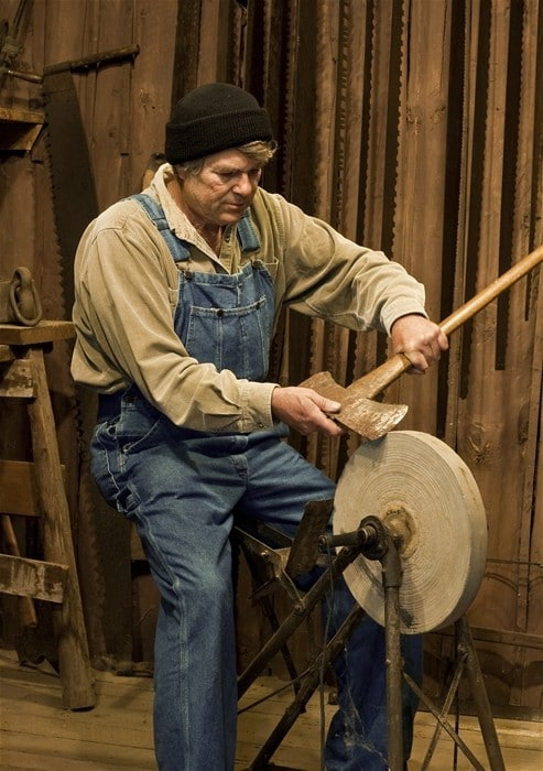 man sharpening an axe on an old pedal powered grinding stone
